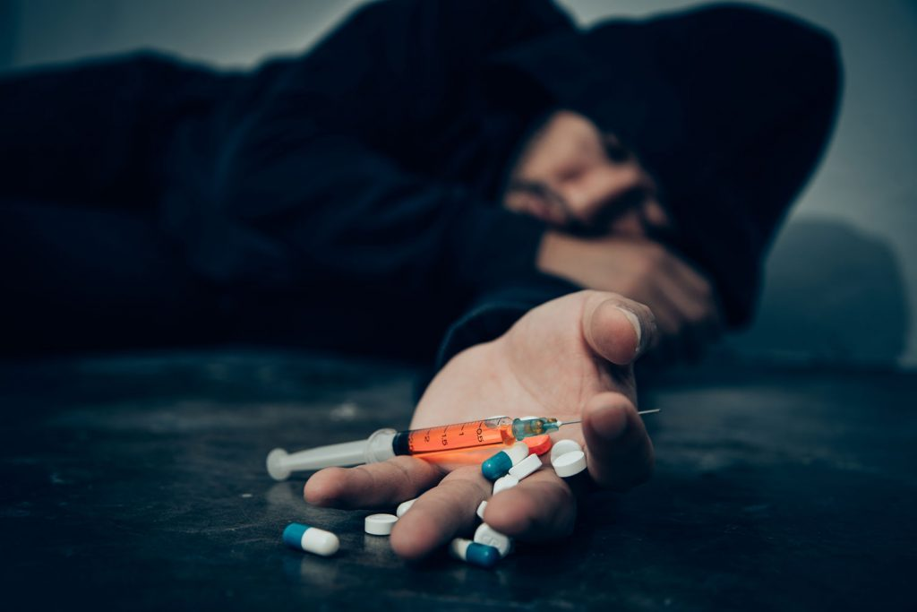 man lying on the floor with pills and syringe on hand
