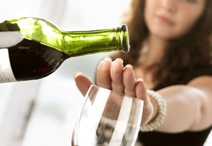 woman puts her hand over wine glass trying to stop drinking alcohol