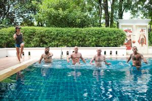 Clients doing physical exercise in a swimming pool at The Dawn Drug Rehab in Thailand
