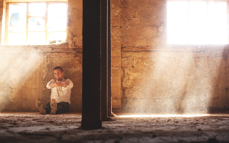 man sitting alone against the wall
