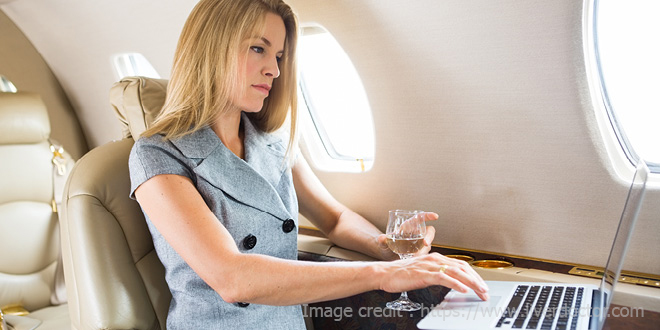 woman working on her laptop and drinking an alcoholic beverage on a plane
