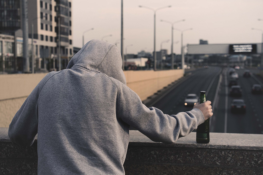 Man in hooded sweater holding an alcoholic beverage on the bridge
