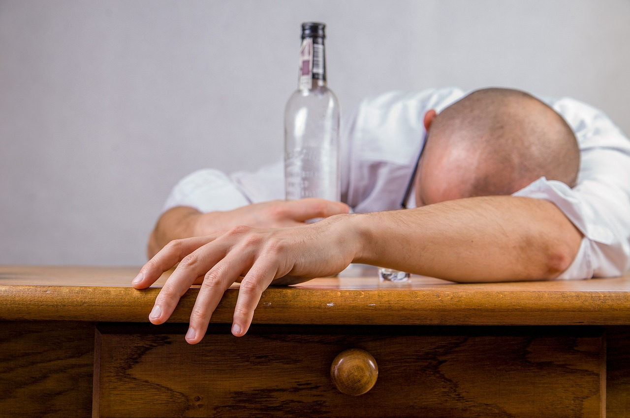 Man passing out on table with an empty bottle - sign of functional alcoholics