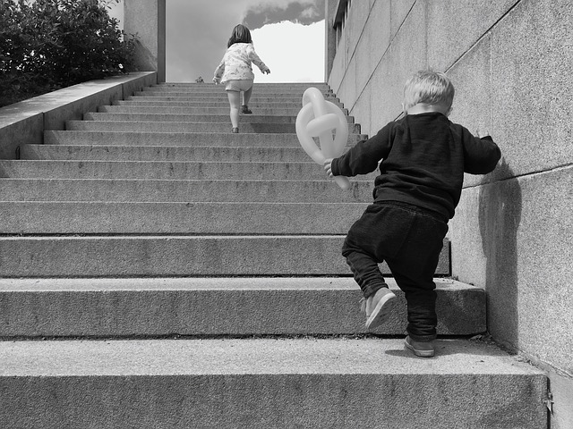 Two kids walking up the stairs