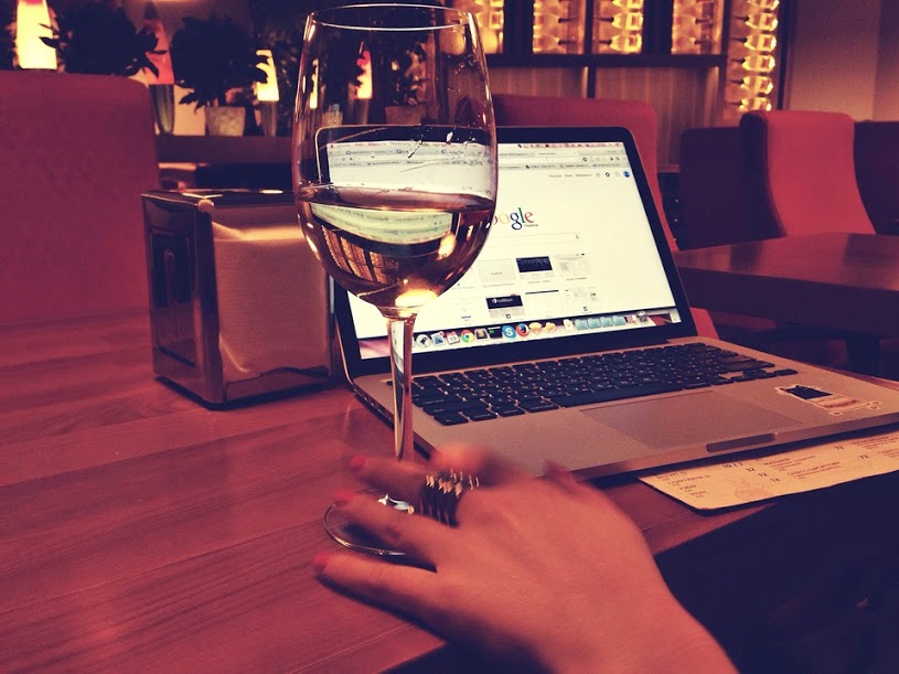 Glass of wine on table with laptop in the background