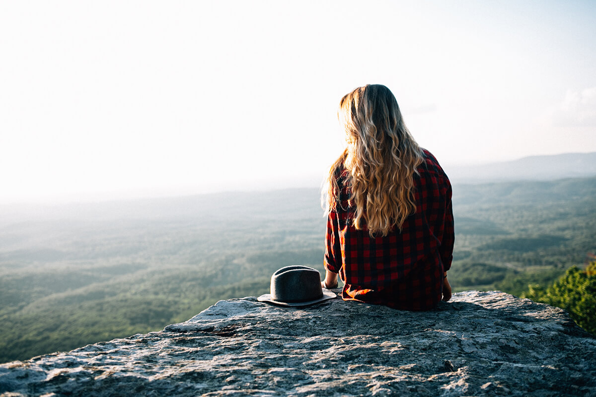 a woman is setting at the edge and considering to travel for the abroad rehab.
