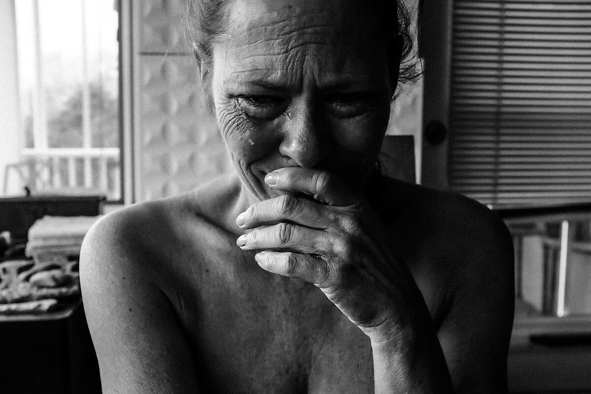 woman crying and feeling depressed inside the room
