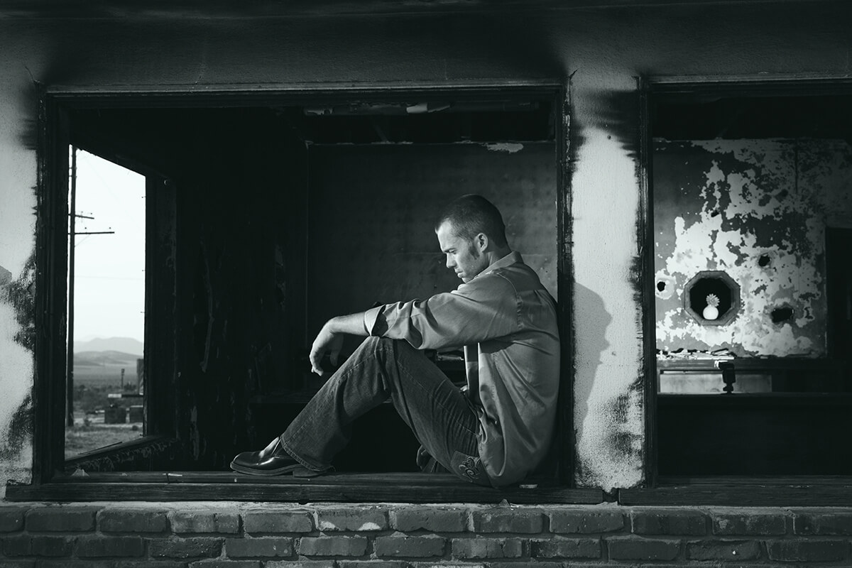 a man sitting on the edge, feels depressed about his life.