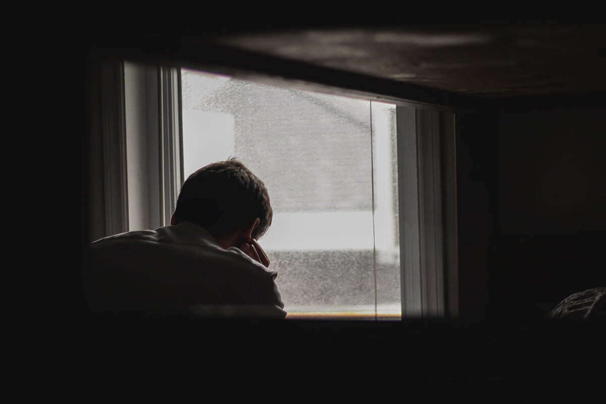 a man is sitting in his room and feeling depressed all the time.