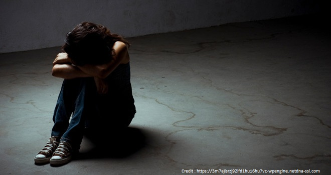 Young girl sitting on the floor crying