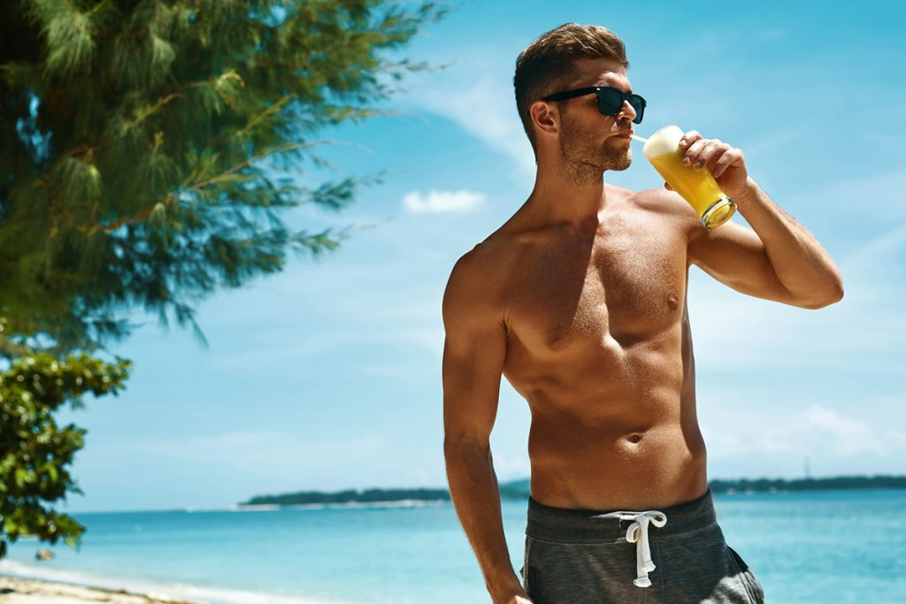 A young expat enjoys a drink on a beach, on a sunny afternoon.