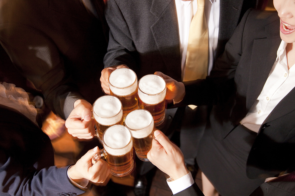Several professionals drink beers together at a bar after work.