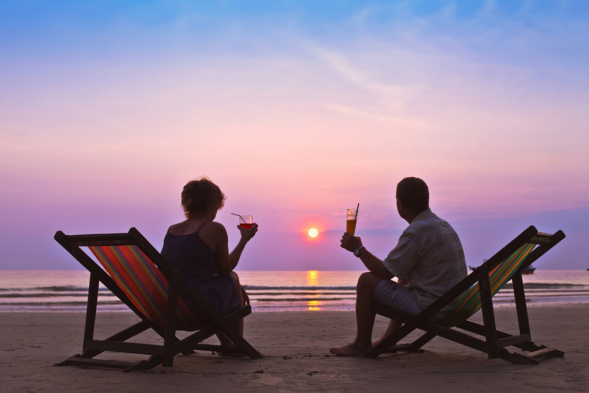 A retired couple have cocktails as they watch a tropical sunset.