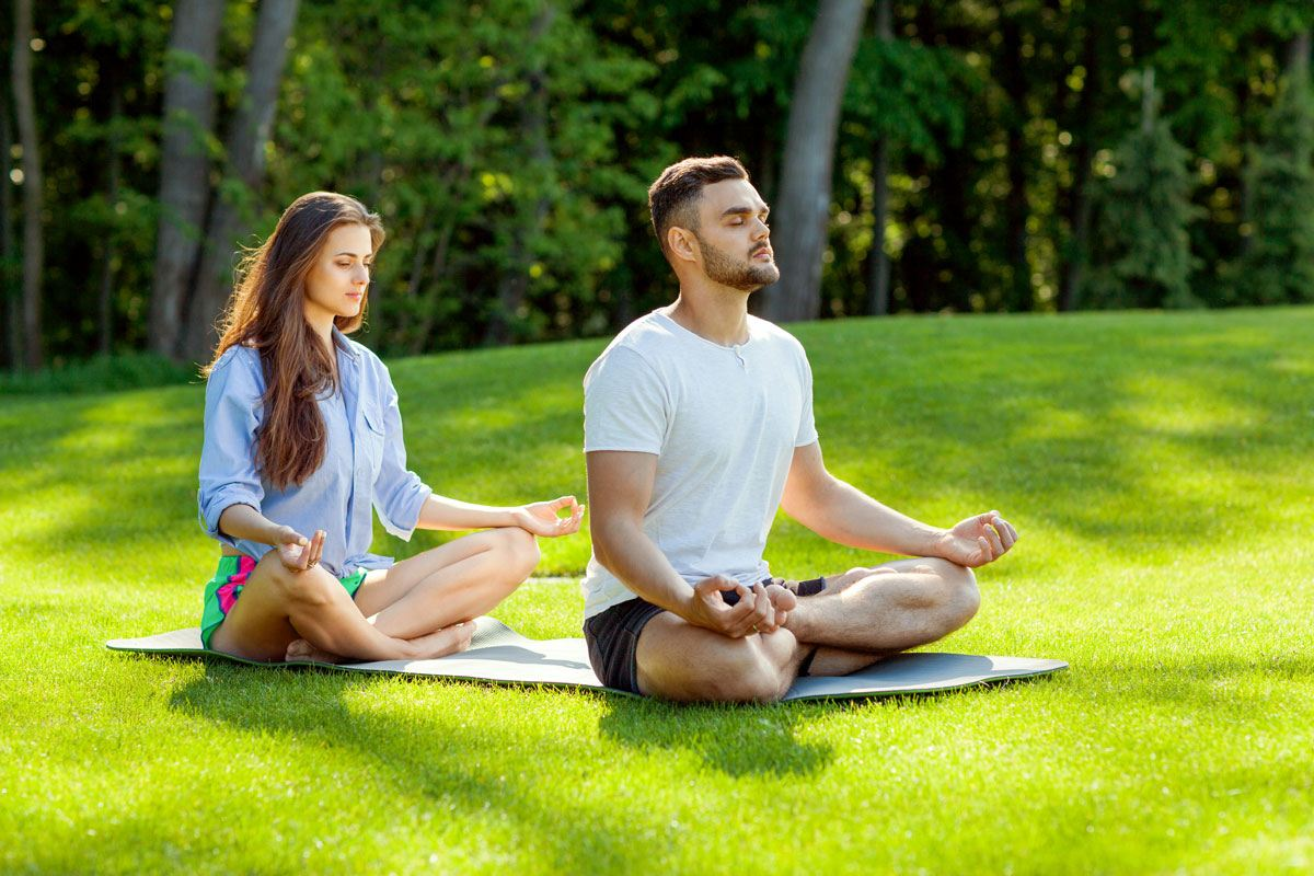A man and woman are doing meditation to practice the mindfulness that helps cope with depression at The Dawn Mental Health Retreat Thailand.