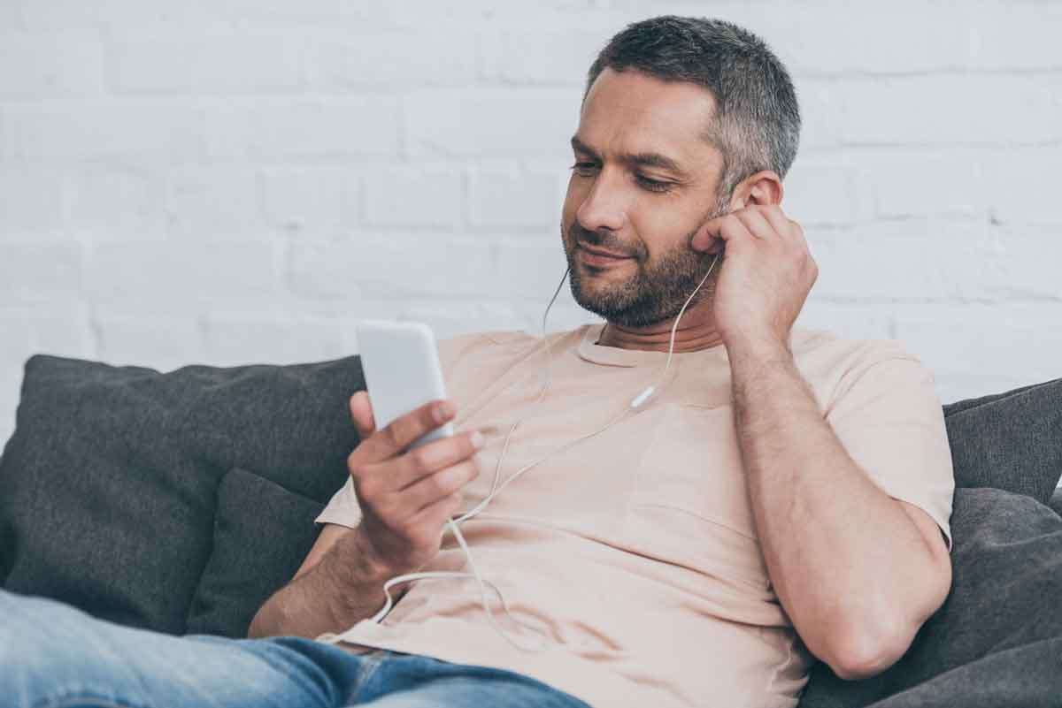 A man is listening to addiction podcast to get some insights for the recovery tools